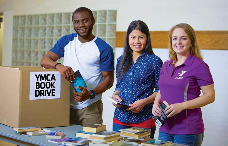 A group of YMCA volunteers stand together at a book drive