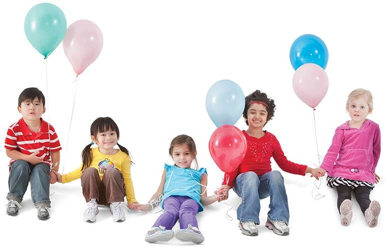 Youth sit and play with inflated balloons together
