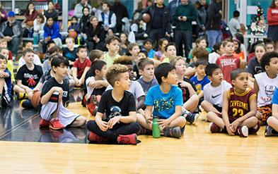 Dozens of children sit together on a basketball court