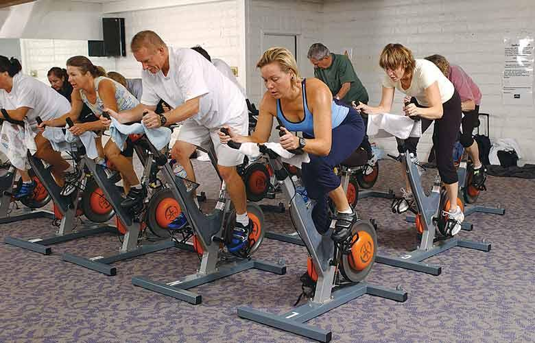YMCA members participate in a spin class, on stationary bikes