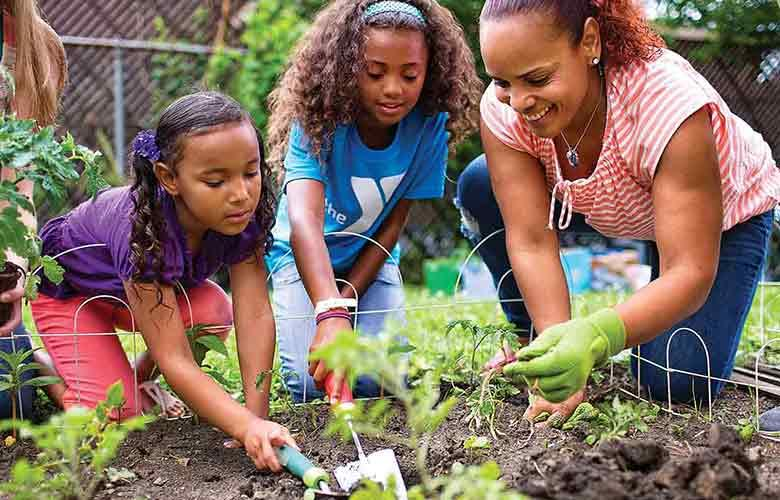 A family works together to plant a garden in the yard.