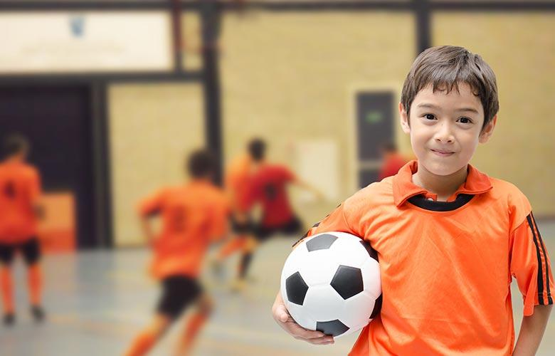Young boy holding soccer ball inside