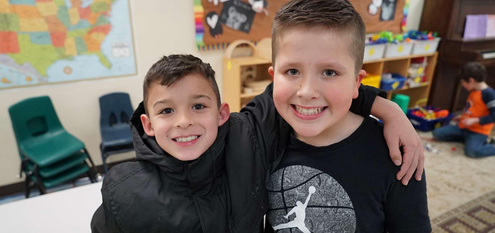 Two boys smiling in a classroom