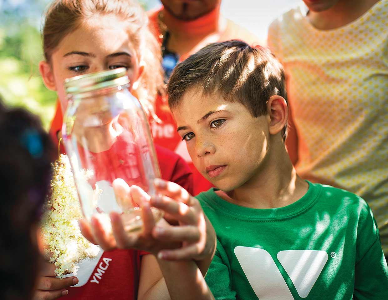 Children at camp examine a butterfly in a mason jar