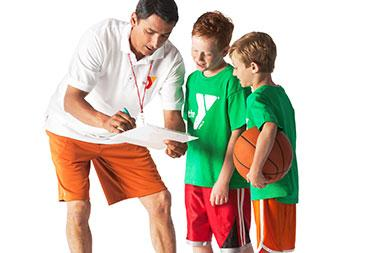 Basketball coach instructs two young boys