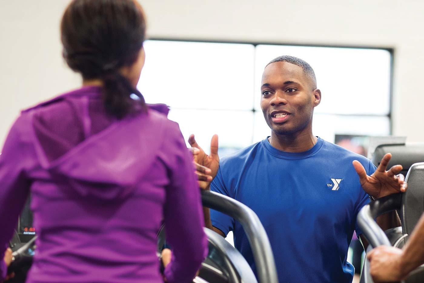 Personal trainer assists member on treadmills