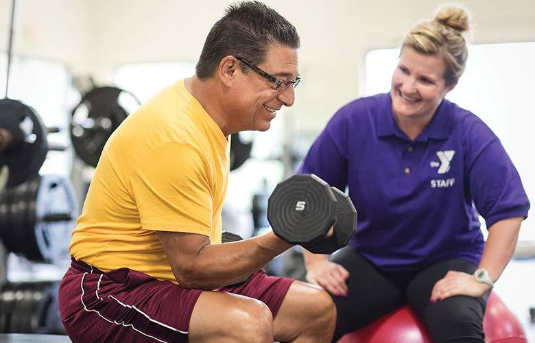 YMCA Personal Trainer assists man lifting weights