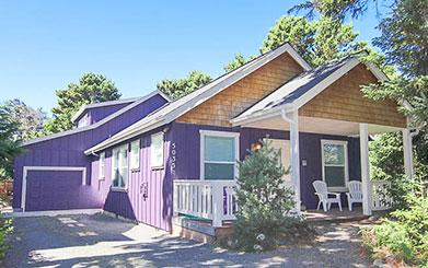Exterior of purple house with porch and patio
