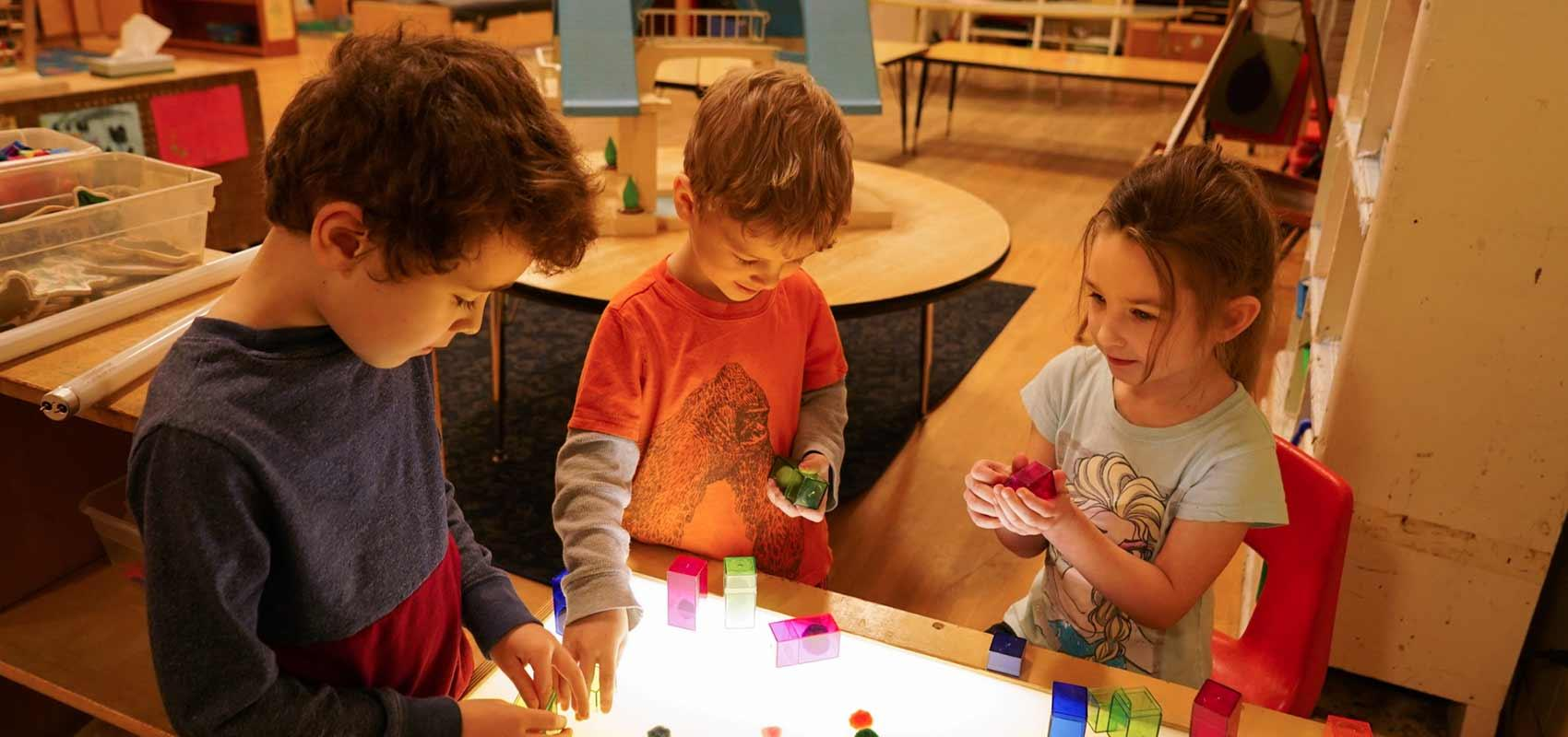 Children play with building blocks in classroom