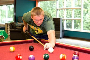 Young boy shoots pool, billiards