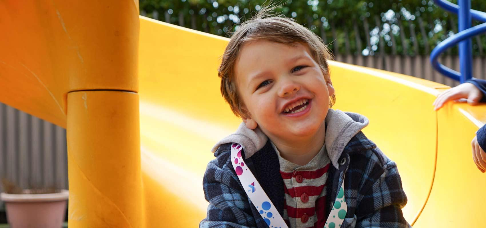 Young boy smiles as he sits on slide at playground