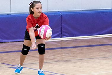 Young girls prepares to serve volleyball