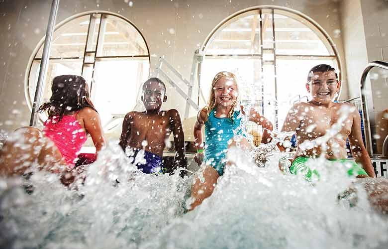 Youth enjoy their time at an indoor pool
