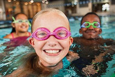 Youth smile in swimming pool, wearing goggles