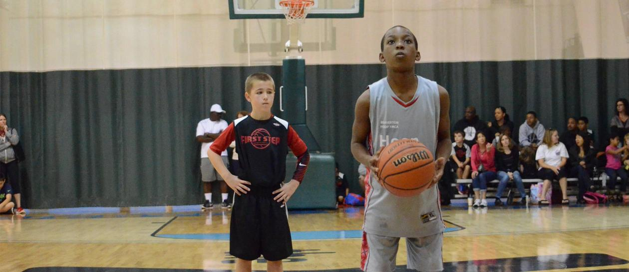Young boy taking a free throw in basketball game