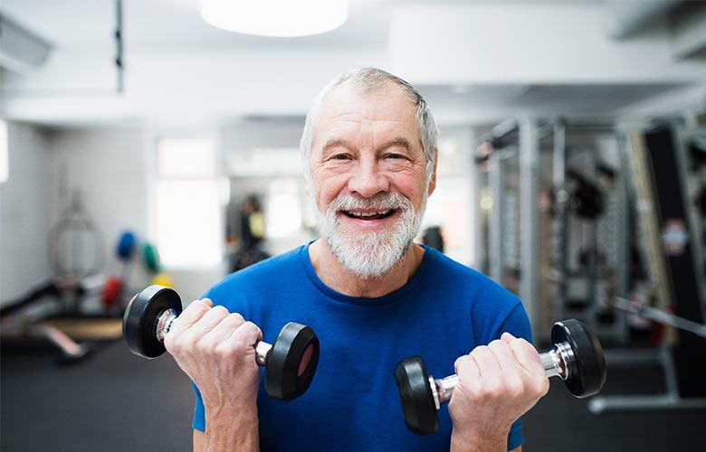 Man curling dumbbells and smiling