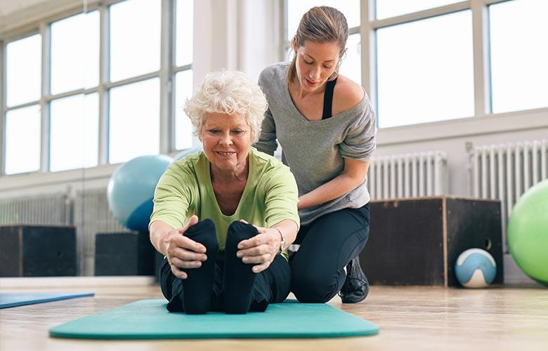 Older woman stretching with a personal trainer