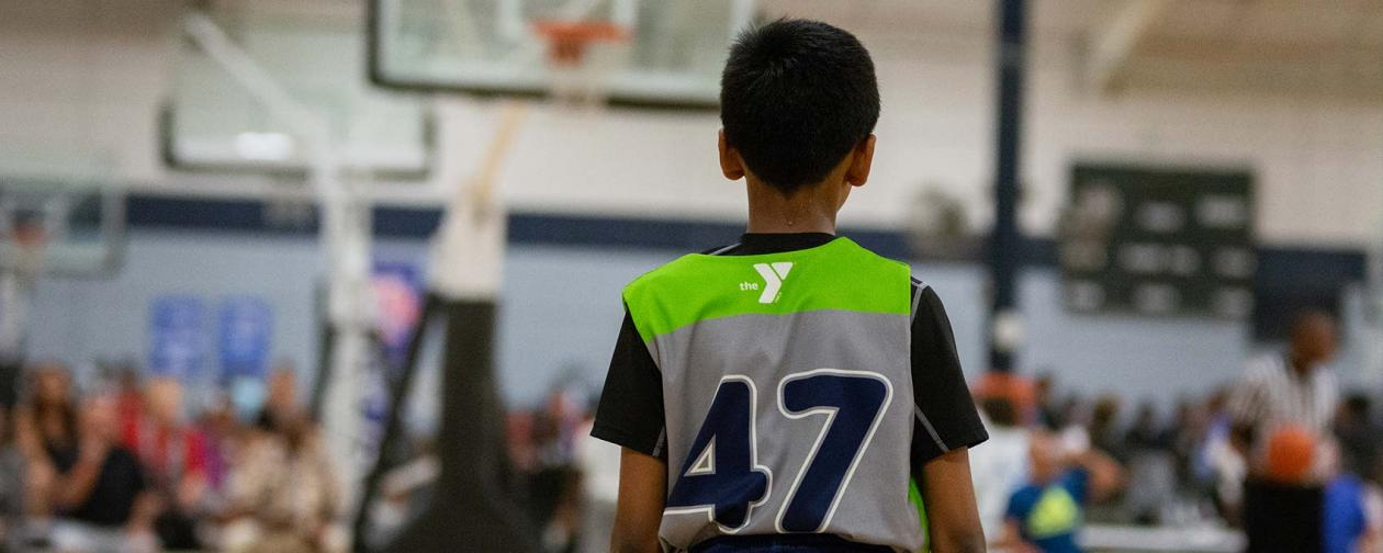 Young boy standing on basketball court