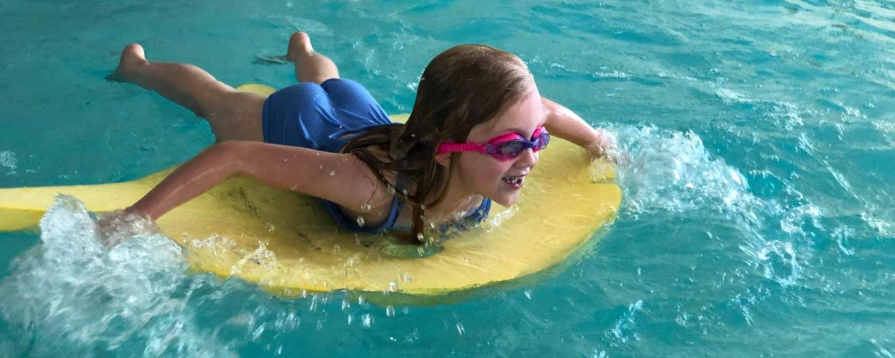 Young girl with goggles on a boogie board in the pool