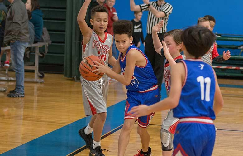 Boy passing basketball to teammate