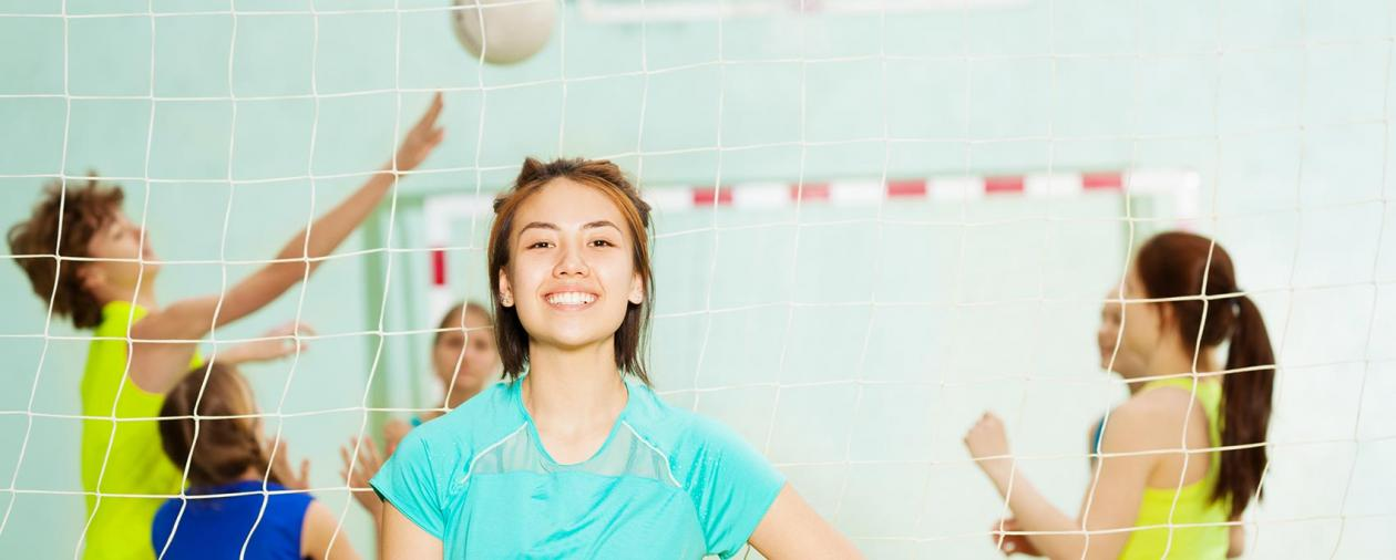 Teen girl smiling on volleyball court