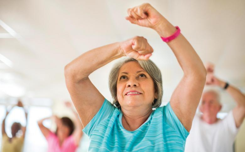 Woman participates in active older adult exercise class