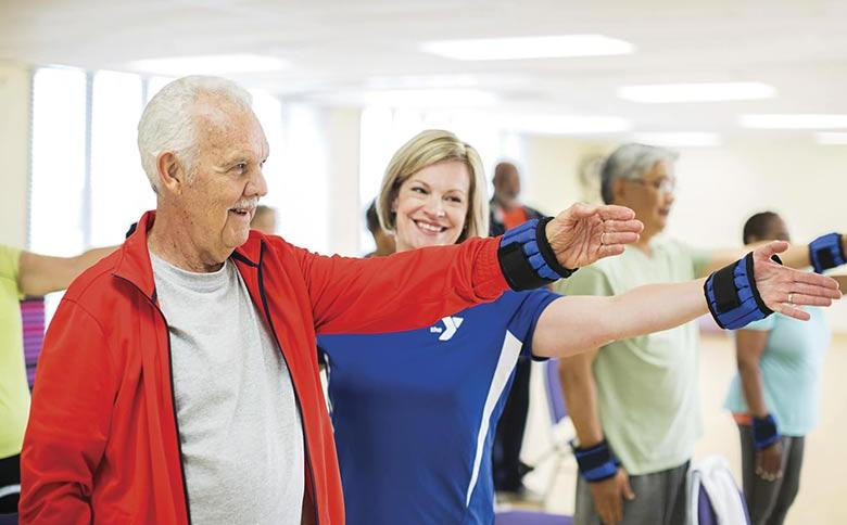 An active older adult receives advice from YMCA personal trainer