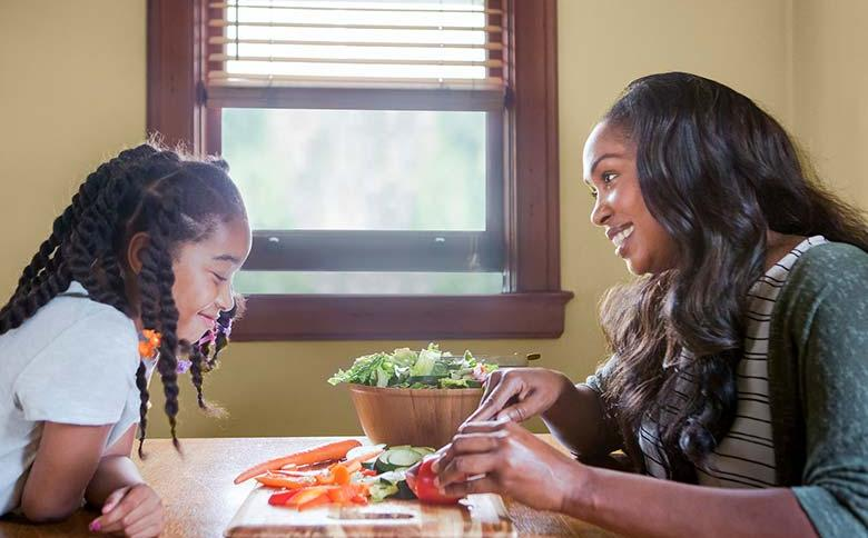 Mom and daughter sit at dinner table discussing healthy food options