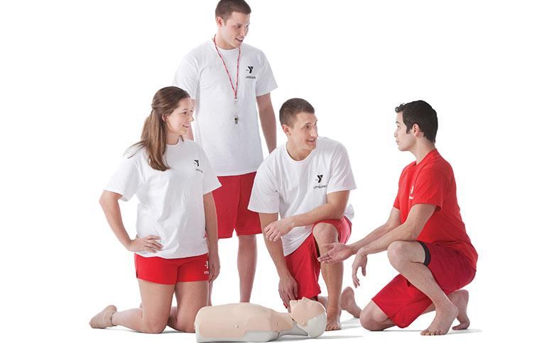 A group of young adults listen to a CPR instructor