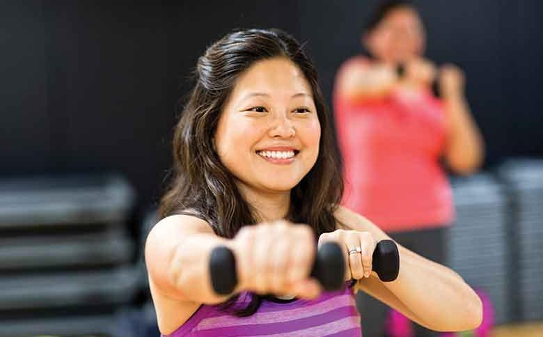 Woman exercises with dumbbells during group exercise class